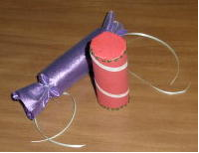 Decorate toilet paper tubes with holiday colors like this construction paper wrapped candy-cane or this firecracker wrapped in purple cloth.