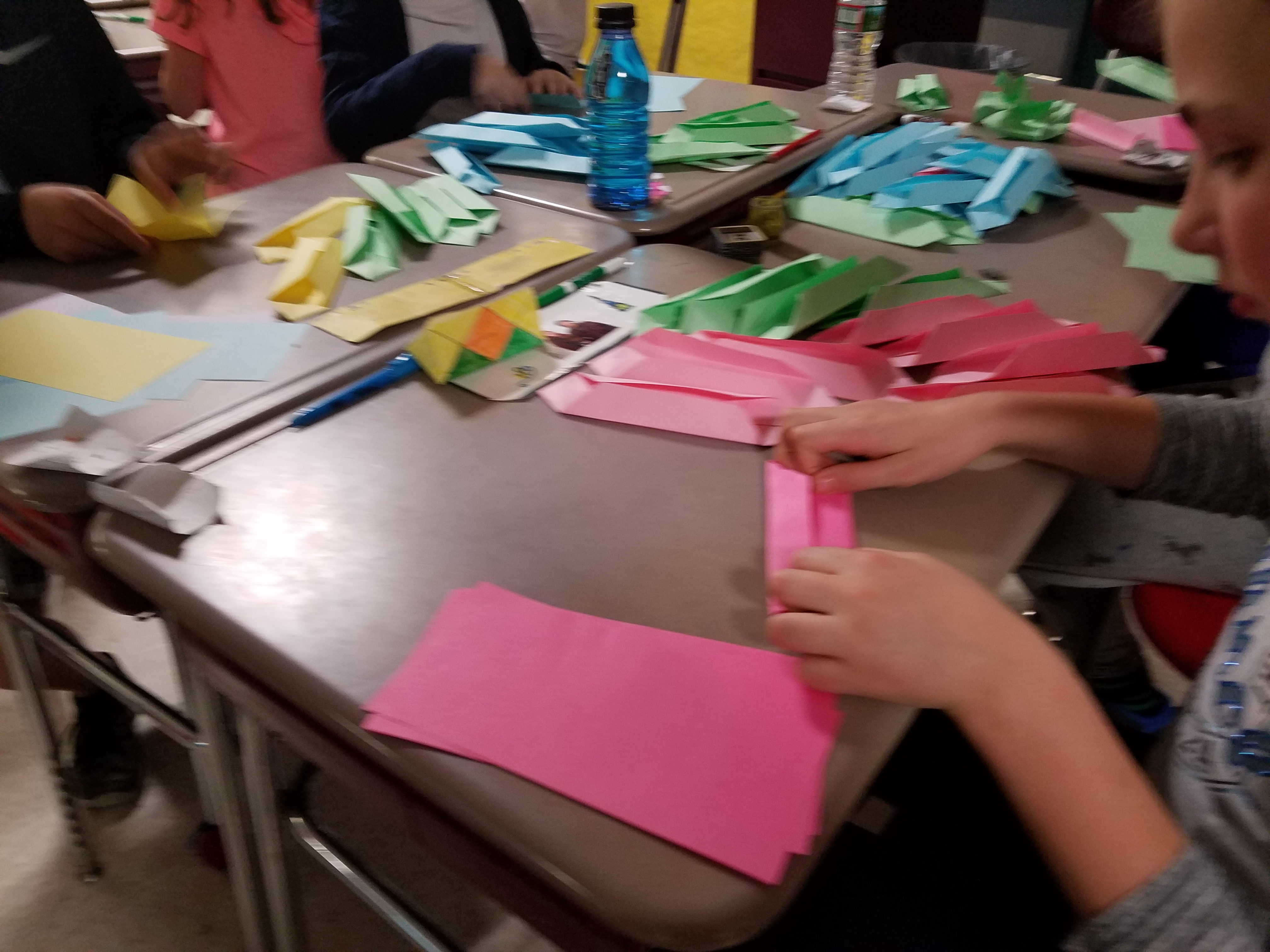 Students fold their 16 papers to create a lotus flower.