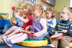 Photo Source: https://www.bigstockphoto.com/image-109208591/stock-photo-group-of-pre-school-children-taking-part-in-music-lesson