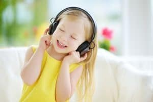 Photo Source: https://www.bigstockphoto.com/image-181438210/stock-photo-cute-girl-wearing-huge-wireless-headphones-pretty-child-listening-to-the-music-schoolgirl-having-f