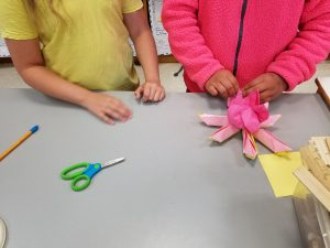 A 4th grade buddy shows a 2nd grade buddy how to create the petals of the lotus flower.